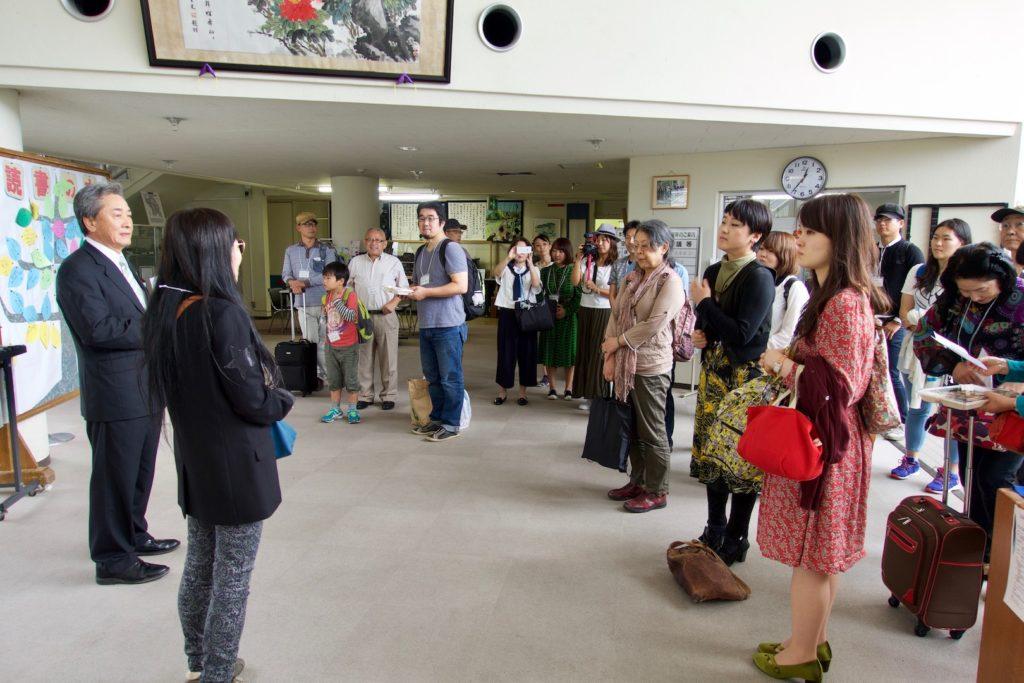 鳥取空港と鳥取駅から貸切りバスで到着した、40名の追憶ツアー参加者を迎える榎本武利町長。