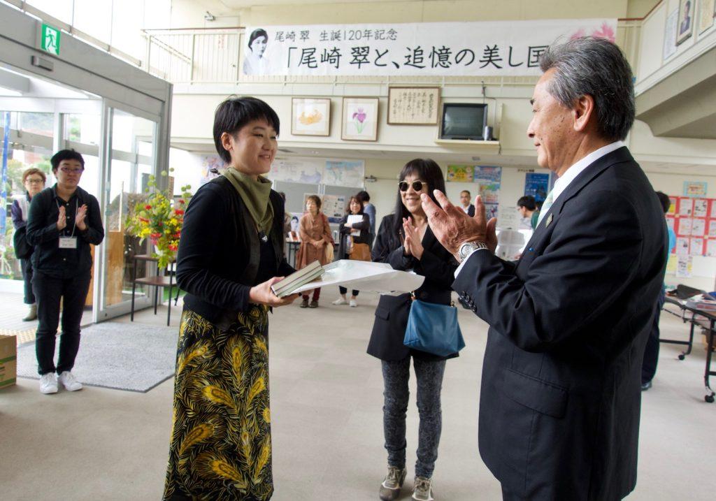 追憶ツアー参加者には『尾崎翠を読む』全3冊が贈られた。代表して受け取るカドカチェトリ順さん。